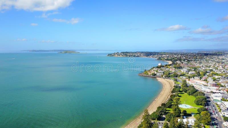 Praia ensolarada com subúrbio residencial no fundo Auckland, Nova Zelândia imagens de stock royalty free
