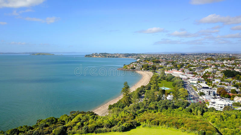 Praia ensolarada com subúrbio residencial no fundo Auckland, Nova Zelândia fotografia de stock