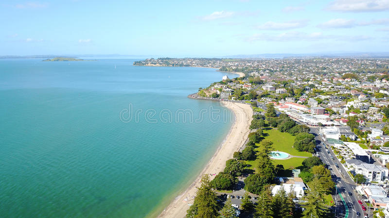 Praia ensolarada com subúrbio residencial no fundo Auckland, Nova Zelândia foto de stock