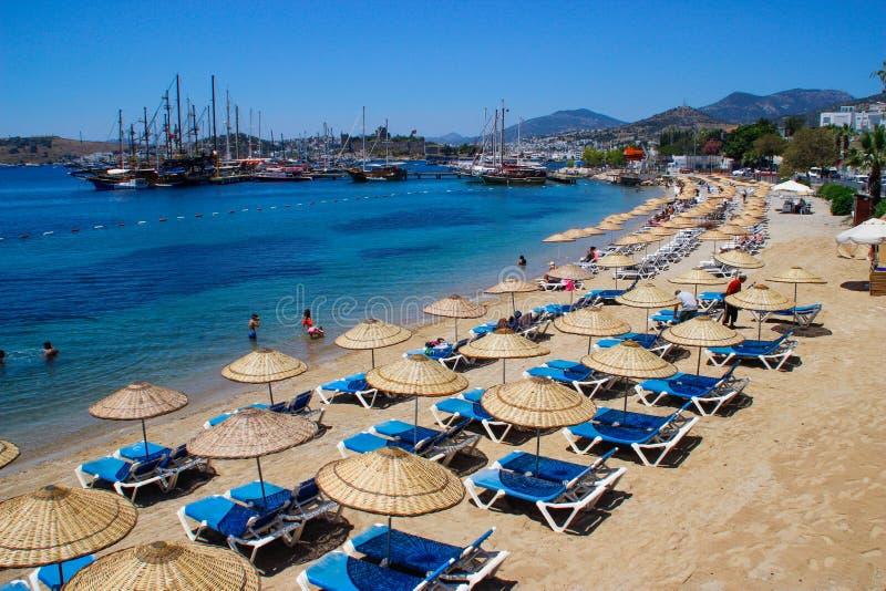 Praia ensolarada em Bodrum com os guarda-chuvas que banham povos na água clara de turquesa Para?so turco fotografia de stock royalty free