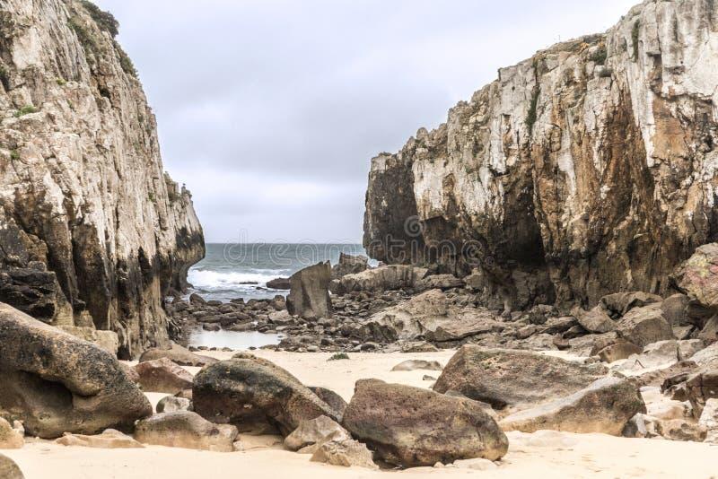 Praia escondida no meio de dois penhascos em um dia nebuloso fotos de stock