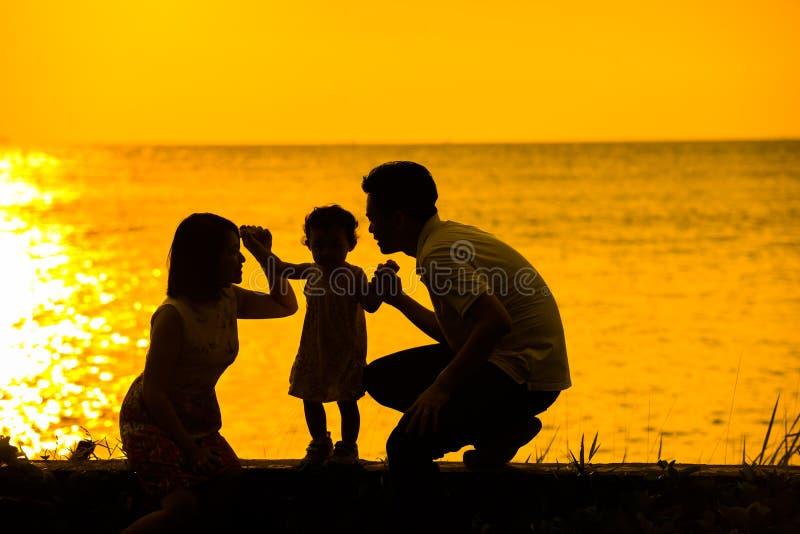 Praia exterior do por do sol da família asiática imagem de stock royalty free