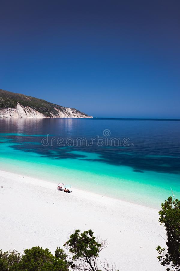 Praia Kefalonia de Fteri, Grécia Família sob o guarda-chuva em Pebble Beach Água do mar esmeralda dos azuis celestes azuis claros imagem de stock royalty free