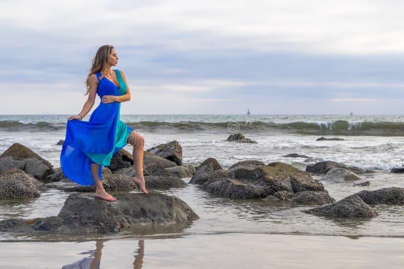 Praia latino moreno bonita de Poses Outdoors On A do modelo no por do sol fotos de stock