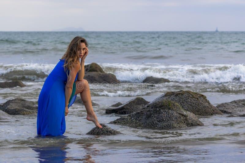 Praia latino moreno bonita de Poses Outdoors On A do modelo no por do sol imagem de stock