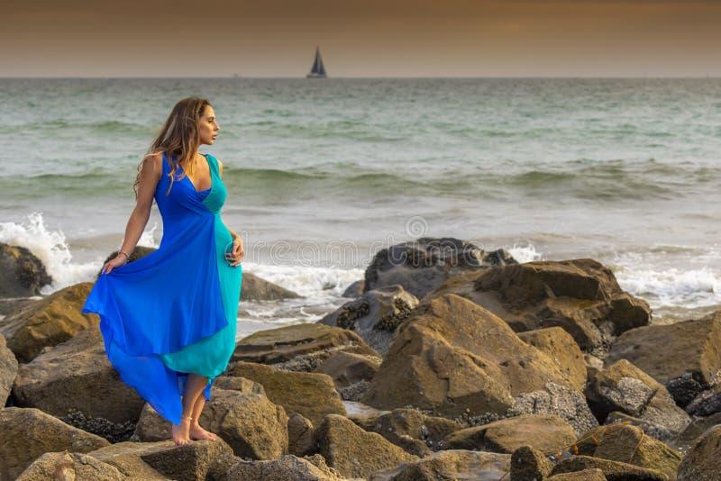 Praia latino moreno bonita de Poses Outdoors On A do modelo no por do sol imagens de stock