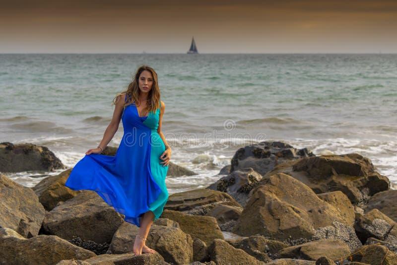 Praia latino moreno bonita de Poses Outdoors On A do modelo no por do sol imagem de stock royalty free