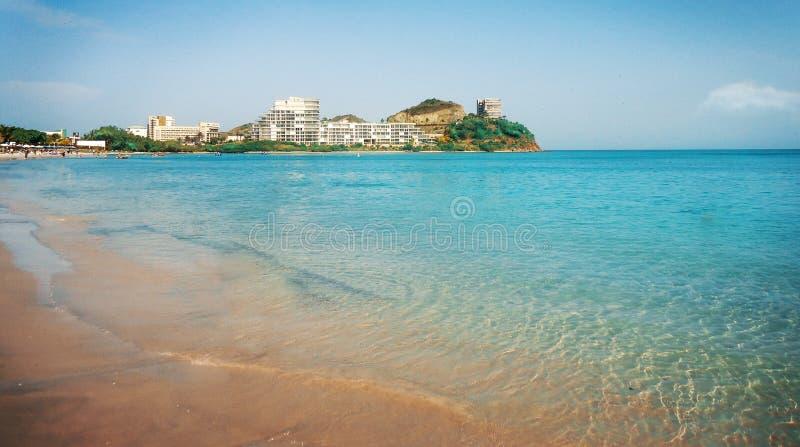 Praia litoral azul do verão com construção e vegetação no fundo fotografia de stock royalty free