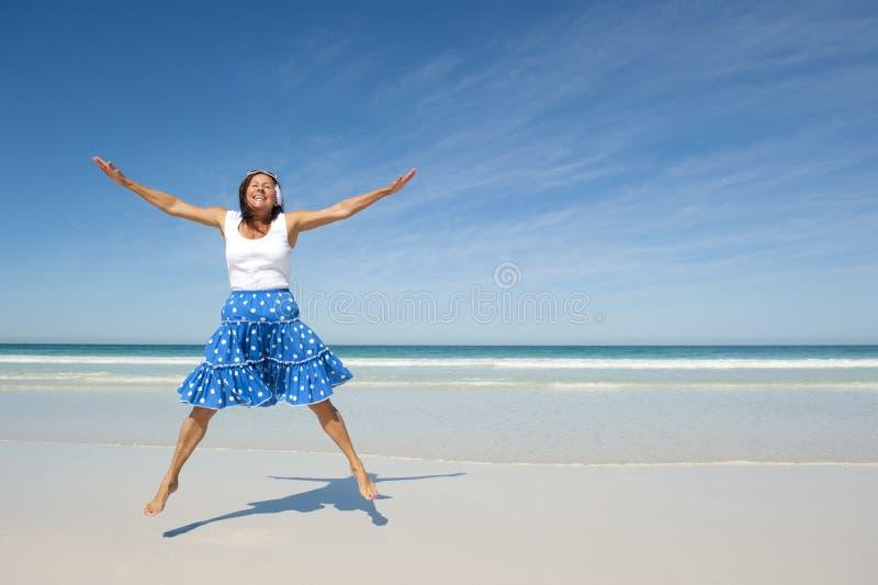 Praia madura de salto feliz da mulher imagem de stock royalty free