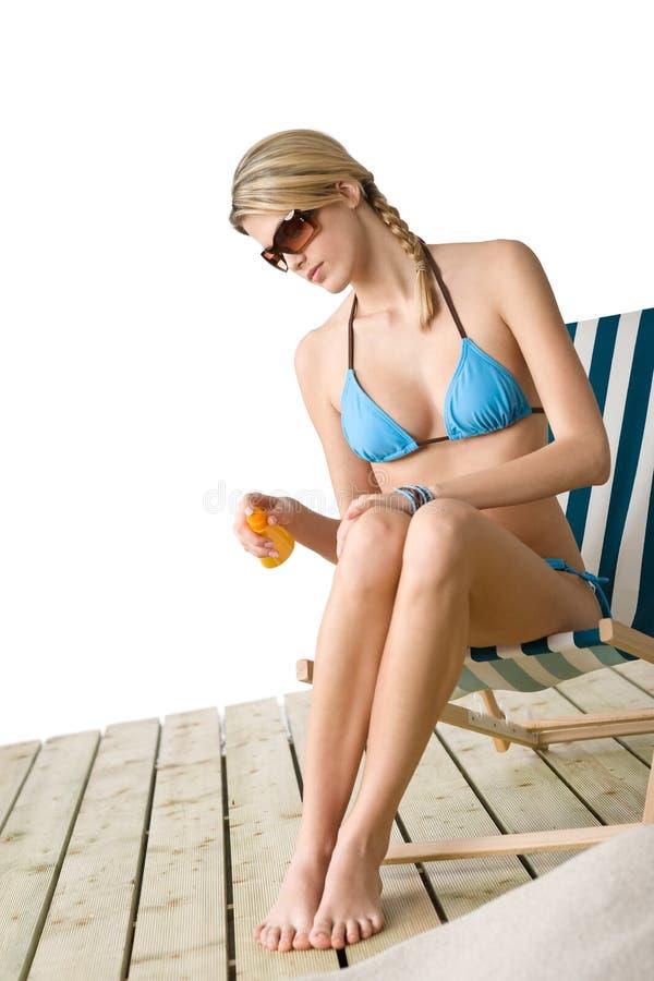 Praia - a mulher nova no biquini aplica a loção do suntan foto de stock
