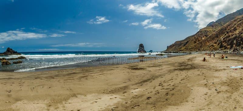 Praia natural longa Benijo com pegadas na areia Rocha da lava na água Horizonte de mar azul, fundo natural do c?u fotos de stock royalty free
