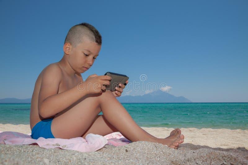 Praia nova de Smartphone do jogo do menino imagens de stock royalty free