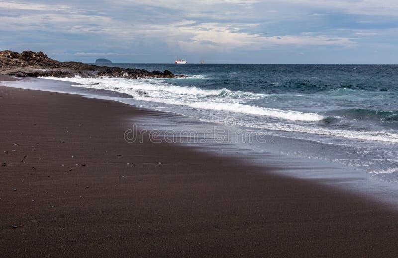 Praia preta da areia em Padangbai, ilha de Bali, Indonésia imagem de stock