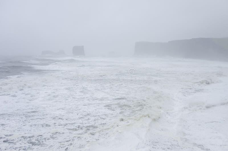 Praia preta Reynisfjara da areia na costa de Oceano Atlântico com foto de stock royalty free