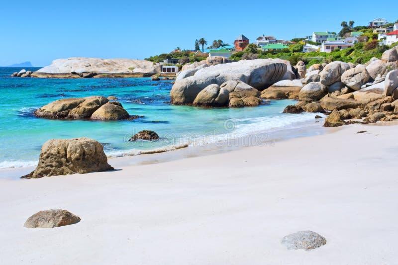 Praia rochosa na frente das casas imagem de stock royalty free