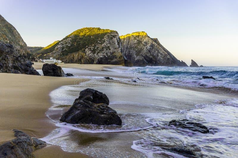 Praia rochosa no nascer do sol, Lagos, Portugal Luz contr?ria imagens de stock