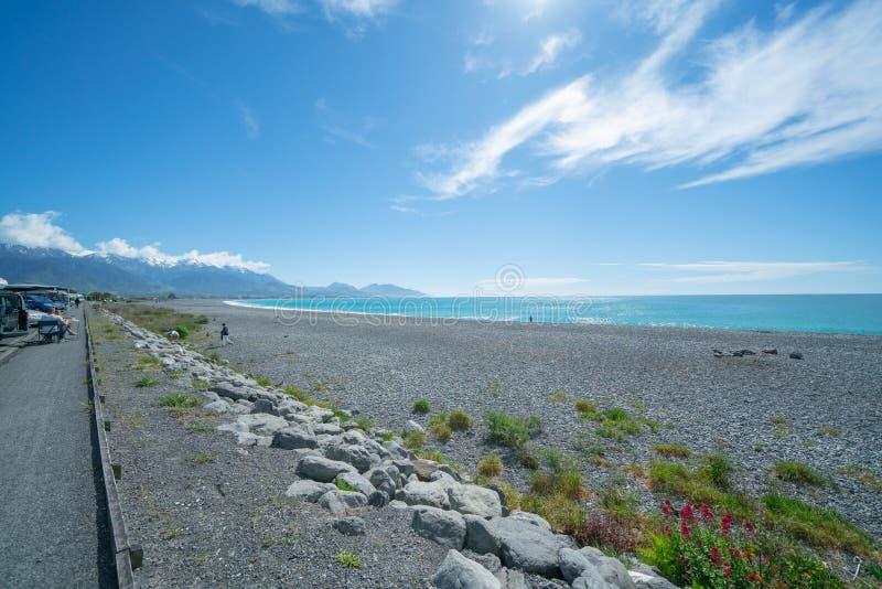 Praia rochoso e mar de Kaikoura sob o céu azul com nuvens brancas foto de stock royalty free