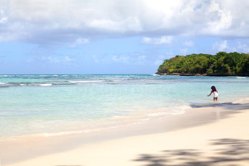 A praia s? da areia branca, o mar azul, as palmeiras verdes, o fundo da ilha e uma menina tocam na ?gua no mar fotos de stock