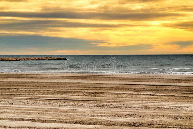 Praia sob o céu tormentoso dourado imagens de stock