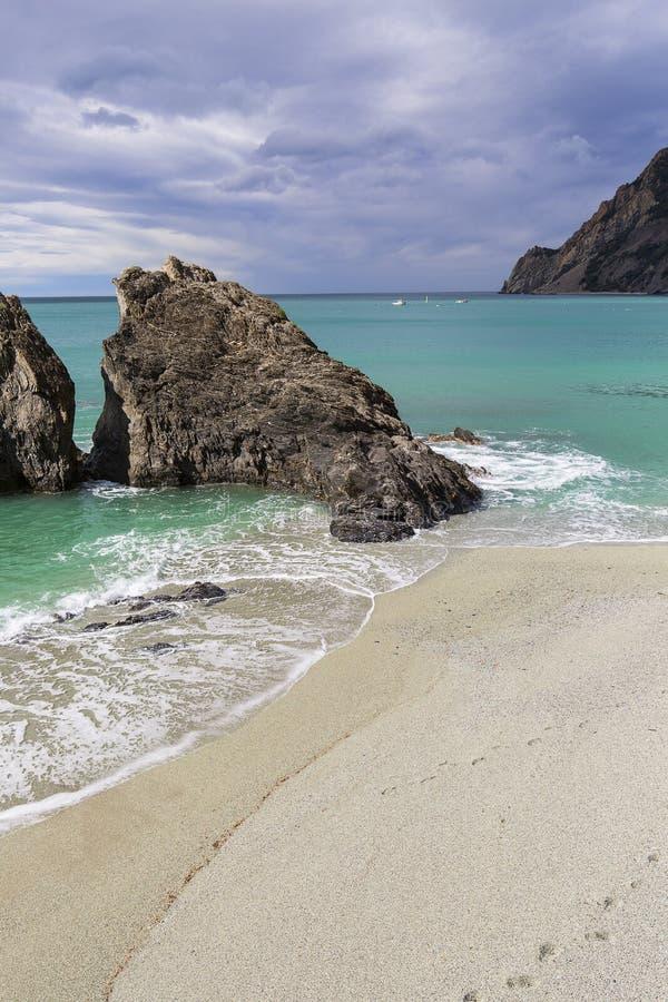 Praia sobre o mar Mediterrâneo, única rocha na água da cor de turquesa, Cinque Terre, Monterosso, Itália fotos de stock