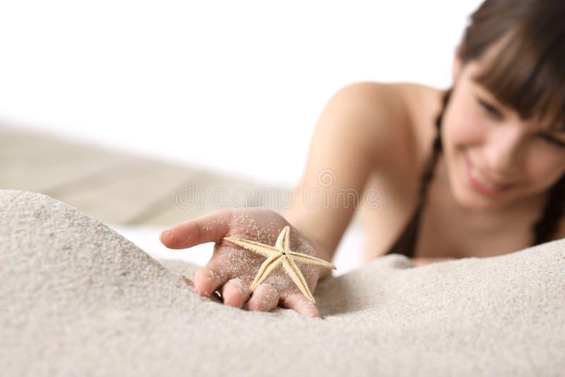 Praia - starfish da terra arrendada da mulher na areia fotografia de stock royalty free