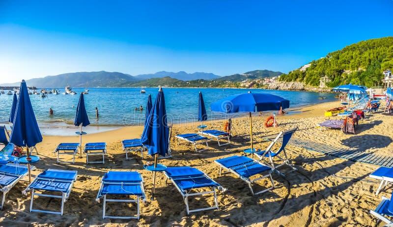 Praia típica das férias com beachchairs e pára-sóis no por do sol foto de stock royalty free