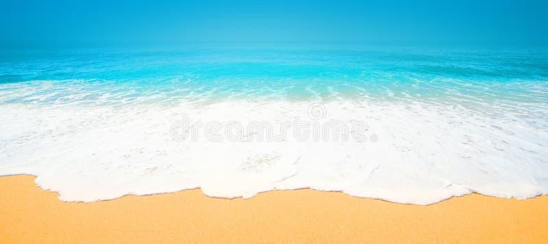 Praia tropical bonita com a onda macia do oceano azul, areia e imagem de stock royalty free