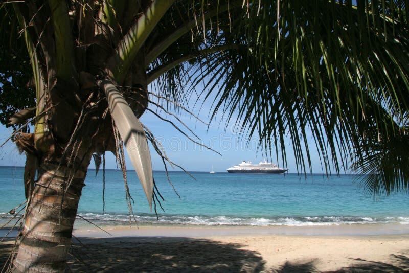 Praia tropical com o navio de cruzeiros no horizonte foto de stock royalty free