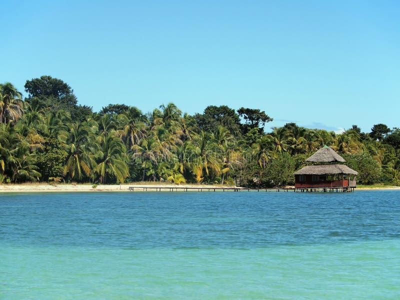 Praia tropical com o restaurante sobre a água foto de stock royalty free