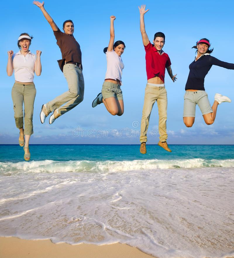 Praia tropical de salto do grupo feliz dos jovens imagens de stock royalty free
