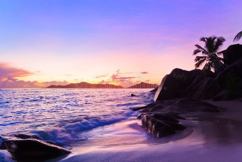 Praia tropical no por do sol imagem de stock