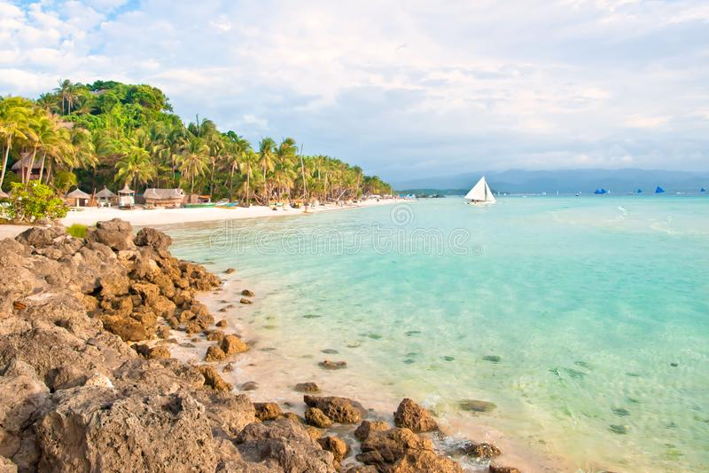 Praia tropical no por do sol com rochas e palmeiras fotografia de stock royalty free