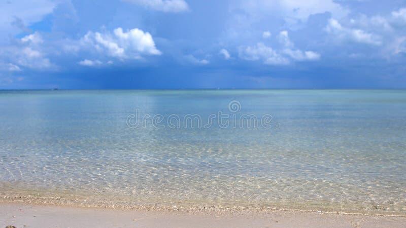 Praia tropical surpreendente Ondas de oceano e fundo do céu nebuloso Areia branca e mar cristal-azul imagens de stock