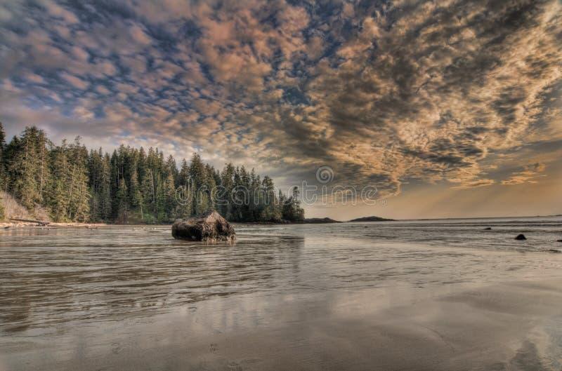 Praia vasta com nuvens surpreendentes e a rocha grande foto de stock