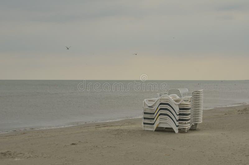 Praia vazia, cadeiras de sala de estar empilhadas imagem de stock