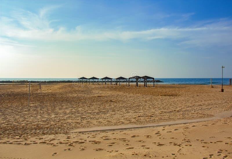 Praia vazia com dosséis do sol e uma rede do voleibol fotografia de stock
