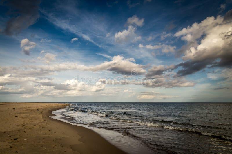 Praia vazia longa da areia na península dos Hel no Polônia com o céu azul dramático, nebuloso imagem de stock