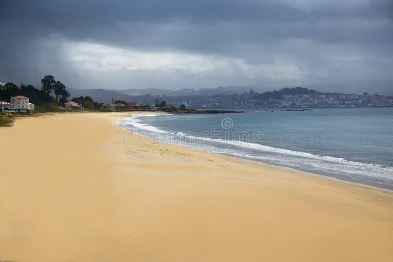 Praia vazia, Oceano Atlântico e céu tormentoso, opinião da cidade imagens de stock royalty free