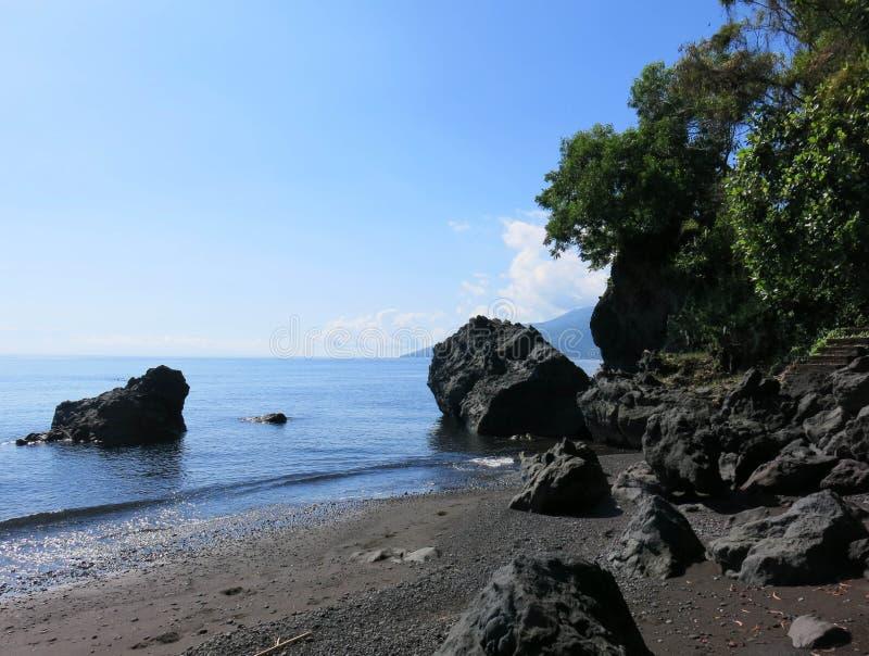 Praia virgem romântica com areia preta Formações rochosas de origem vulcânica penhascos de formas abstratas salientes sobre a sup fotografia de stock