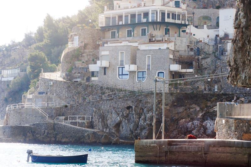 Praiano, побережье Амальфи, Италия, Европа - взгляд дома на горах утесов и шлюпке рыболовов в море стоковые фотографии rf
