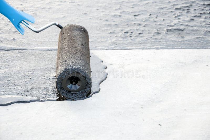 Praimer do betume da pintura do trabalhador do Roofer na superfície concreta por t foto de stock