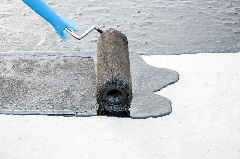 Praimer för bitumen för Rooferarbetarmålning på konkret yttersida vid t royaltyfri foto