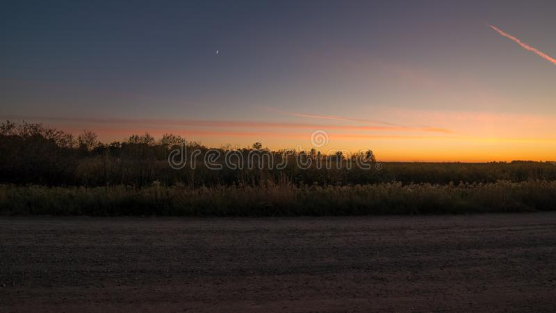 Prairie grassland and rural rustic gravel road landscape at sunset with orange, yellows, and blues in sky - at the Crex Meadows Wi. Ldlife Area stock photography