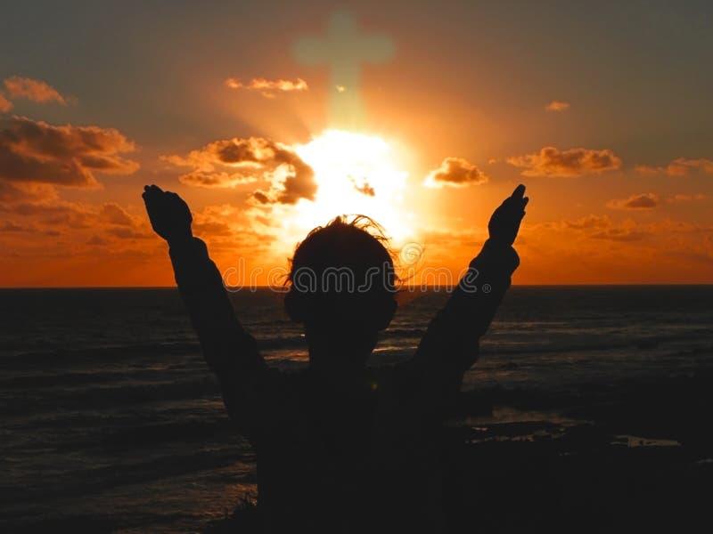 Praising God. A child raising their hands to the setting sun praising God