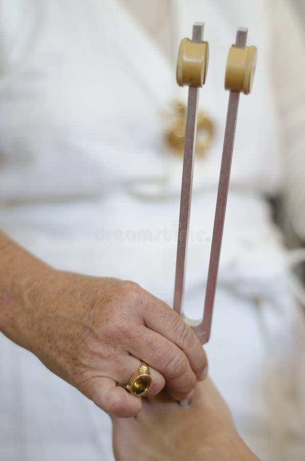 Praktiker, der heilende Stimmgabelbehandlung gibt. lizenzfreie stockfotografie