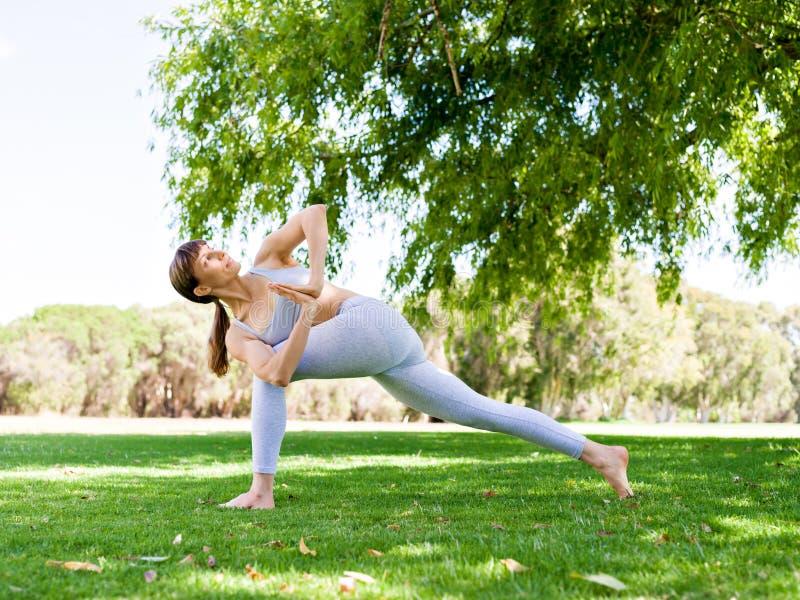 Praktisera yoga för ung kvinna i parkera royaltyfri foto