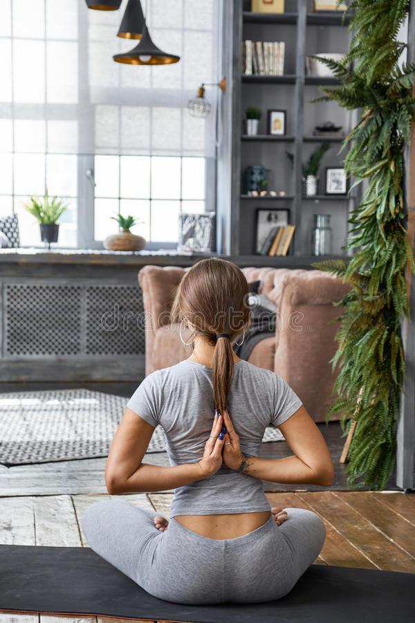 Praktiserande avancerad yoga för kvinna i vardagsrummet hemma En serie av yoga poserar royaltyfri fotografi