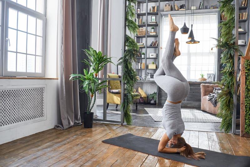 Praktiserande avancerad yoga för kvinna i vardagsrummet hemma En serie av yoga poserar royaltyfri foto