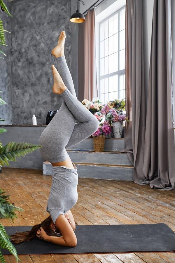 Praktiserande avancerad yoga för kvinna i vardagsrummet hemma En serie av yoga poserar royaltyfria bilder