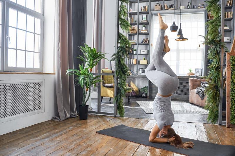 Praktiserande avancerad yoga för kvinna i vardagsrummet hemma En serie av yoga poserar royaltyfri bild